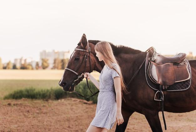 自然の中で夏に茶色の馬の横を歩く長い髪の少女。