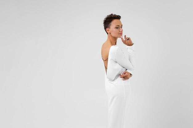 Молодая красивая девушка с короткими темными волосами в длинном белом платье с открытой спиной стоит спиной к камере