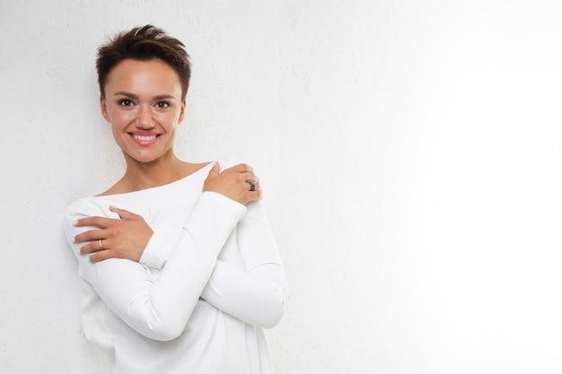 Молодая красивая девушка с короткими темными волосами в длинном белом платье с открытой спиной стоит у белой стены