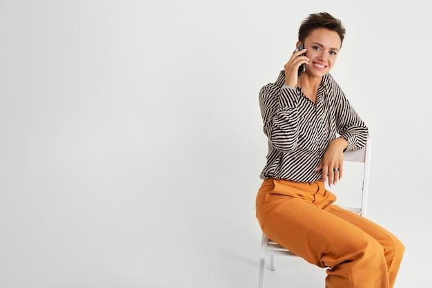 Молодая красивая девушка с короткими темными волосами, косметикой в черно-белой полосатой рубашке, коричневых брюках и туфлях сидит на стуле с телефоном в руках и думает.