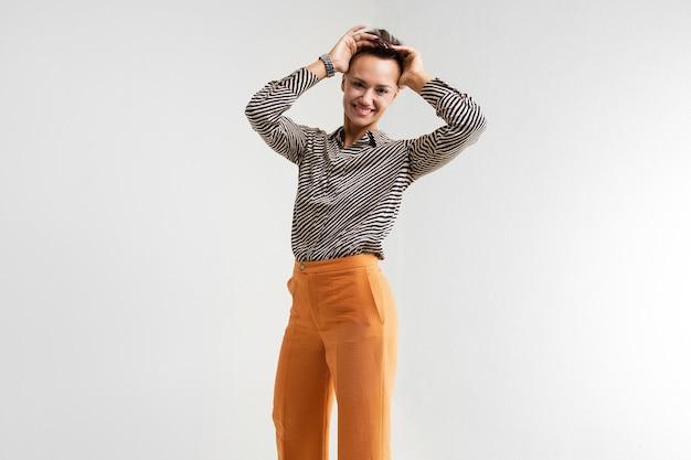 Молодая красивая девушка с короткими темными волосами, макияж в черно-белой полосатой рубашке, коричневые брюки и туфли стоит и улыбается.