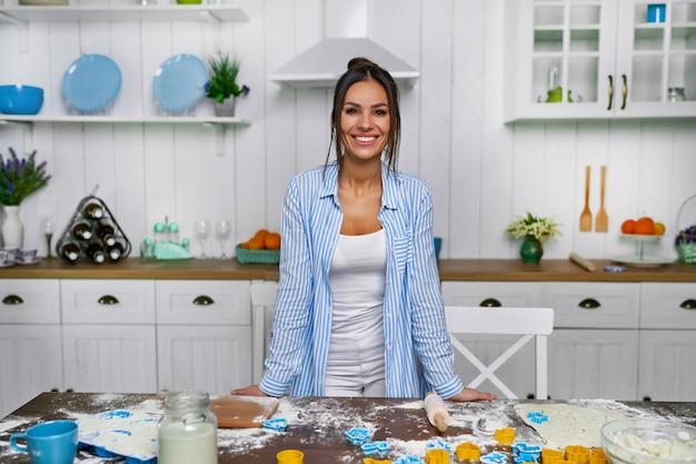 若い美しい主婦が台所のテーブルに立って、羽を焼きます。