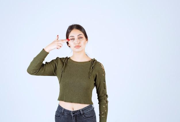 彼女の頭を指している緑のブラウスの若い美しいモデル
