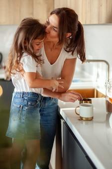 若い美しい母親と泣いている娘がスタイリッシュな家庭の台所でココアを準備しています。