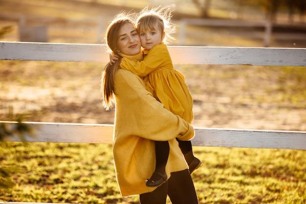 若い美しい母親が秋の公園で散歩中に彼女の手で彼女のかわいい小さな娘を保持しています