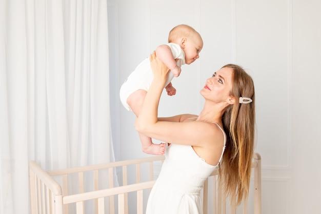 아름 다운 젊은 어머니는 어머니의 날 침대 옆에 서있는 보육원에서 그녀를 들어 올리는 팔에 6 개월 된 딸을 보유하고 있습니다.