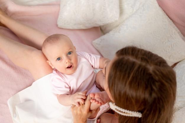 若い美しい母が白いベッドの上で膝の上に6か月の娘を抱きしめ、遊んでキスした