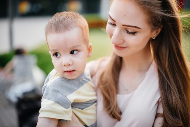 Молодая красивая мать целует и обнимает своего маленького сына во время заката в парке. счастливая семейная прогулка в парке.