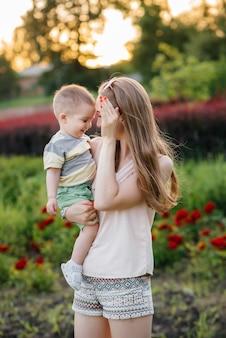 若い美しい母親は、公園で日没時に彼女の幼い息子を演じて抱きしめます。幸せな家族が公園を散歩します。