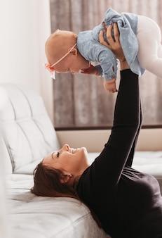 若い美しい母親は、明るい部屋で彼女の女の赤ちゃんと遊んでいます。女性は娘を腕に抱きます