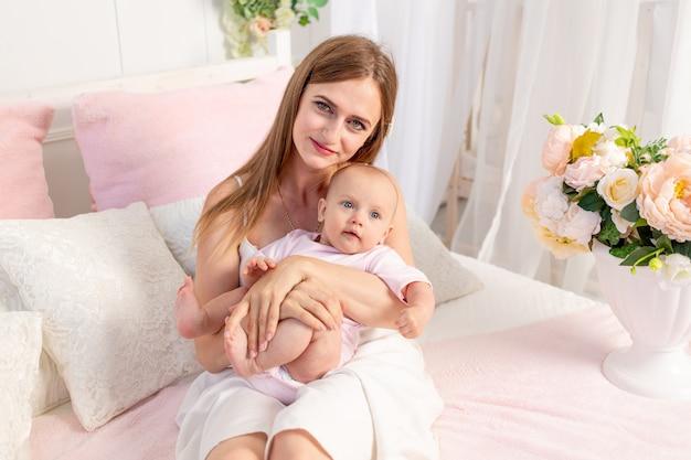 生後6か月の娘を持つ若い美しい母が白い花のベッドに座って抱擁します。