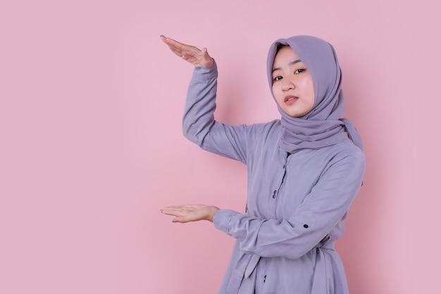 目に見えないアイテムを示す若い美しいイスラム教徒の女性