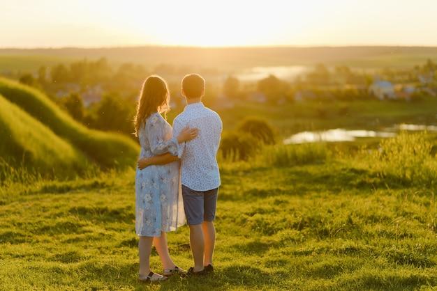 긴 드레스와 일몰 언덕에 함께 서있는 그녀의 남편에 젊은 아름 다운 임신 한 여자. 행복한 가족