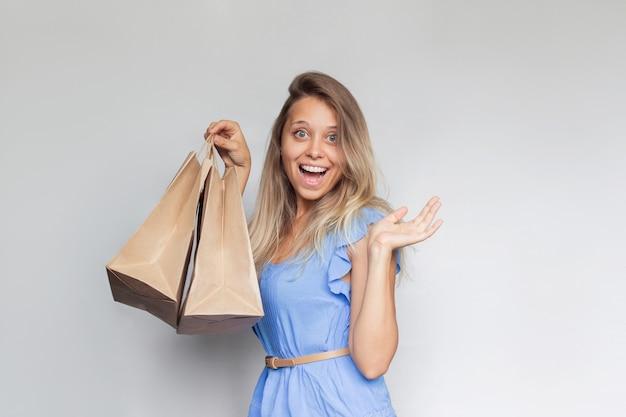 Молодая красивая улыбающаяся жизнерадостная блондинка в синем платье держит в руке бумажные эко-пакеты