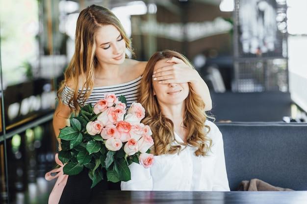 Молодая красивая дочка-подросток закрывает маме глаза и дарит ей букет роз на летней террасе кафе в повседневной одежде.