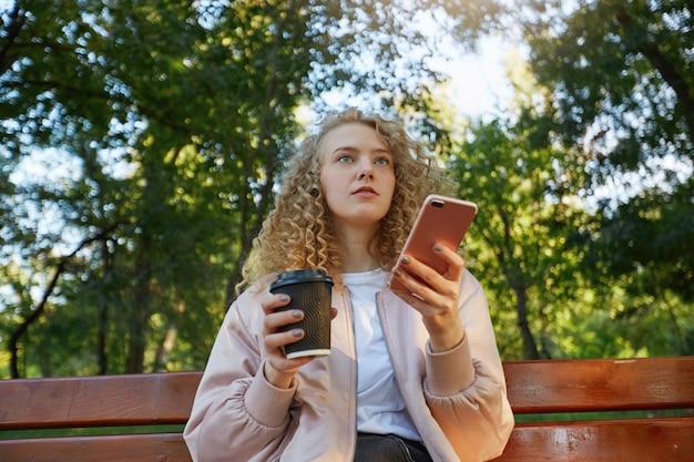 Молодая красивая женщина блондинка сидит на скамейке в парке, пьет кофе