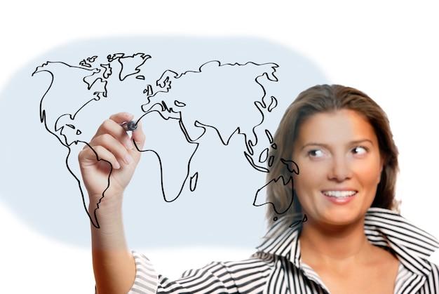 Молодая красивая женщина рисует карту мира на белом фоне