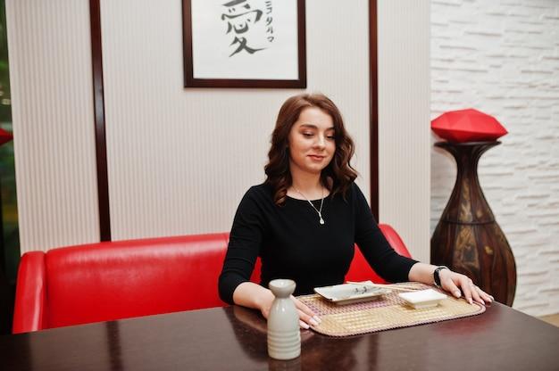 전통적인 일본 레스토랑에서 초밥을 먹는 젊은 아름다운 여자