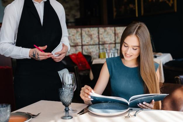 Молодая красивая женщина в прекрасном ресторане просматривает меню и делает заказ молодому официанту в стильном фартуке. обслуживание клиентов.