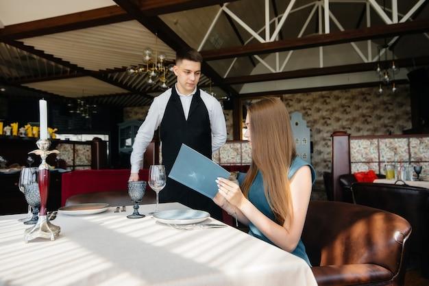고급 레스토랑에서 젊은 미녀가 메뉴를 보고 세련된 앞치마를 입은 젊은 웨이터에게 주문을 합니다. 고객 서비스.