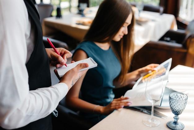 高級レストランの若い美女がメニューを見て、おしゃれなエプロンで若いウェイターに注文。顧客サービス。