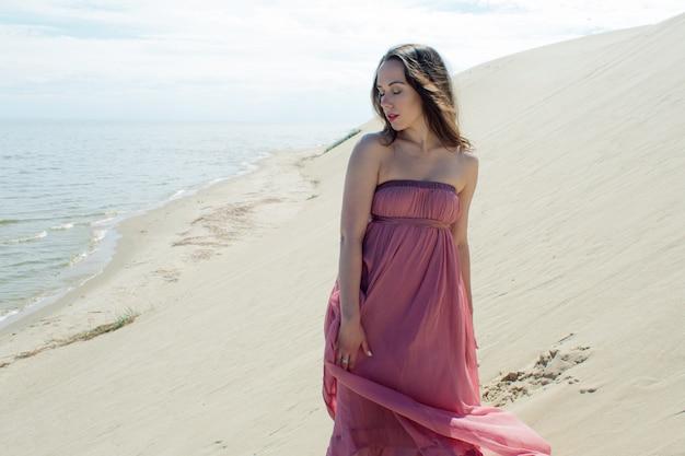 Молодая красивая женщина в розовом платье гуляет по песчаным дюнам