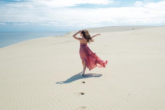 분홍색 드레스에 아름 다운 젊은 여자는 모래 언덕에 산책
