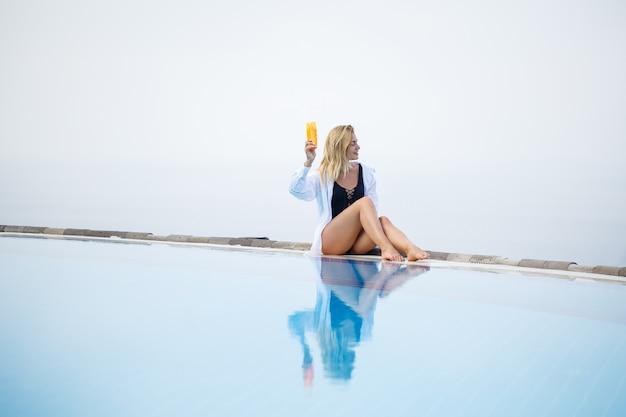 水着姿の若い美女がプールの近くに座り、日焼け止めで肌を塗ります。夏のスキンケア。高品質の写真
