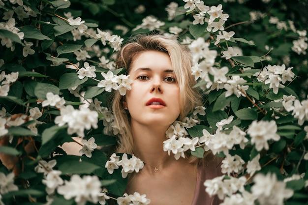 花の間のジャスミンの茂みの若い美しい女性。ピュアスキン、フレグランスのコンセプト、ナチュラルコスメ