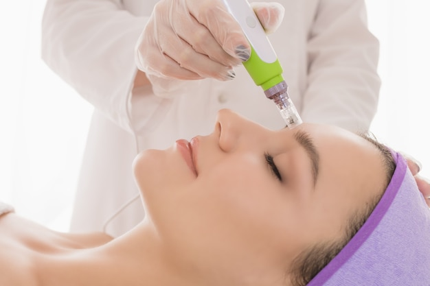 Молодая красивая женщина в кабинете косметолога получает фракционную мезотерапию для лица.