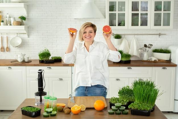 若い美しい女性が果物を切って、テーブルの上の台所でマイクログリーンと果物で作られたビタミンスムージーを求めて笑っています。