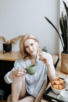Молодая красивая женщина завтракает дома в яркой стильной кухне у окна.