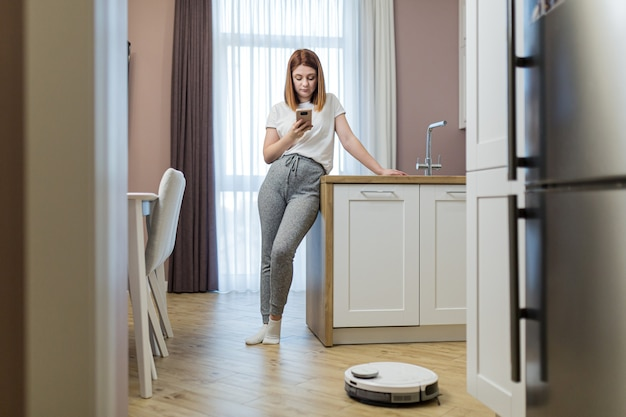 Молодая красивая женщина отдыхает от работы по дому, когда робот-пылесос убирает квартиру