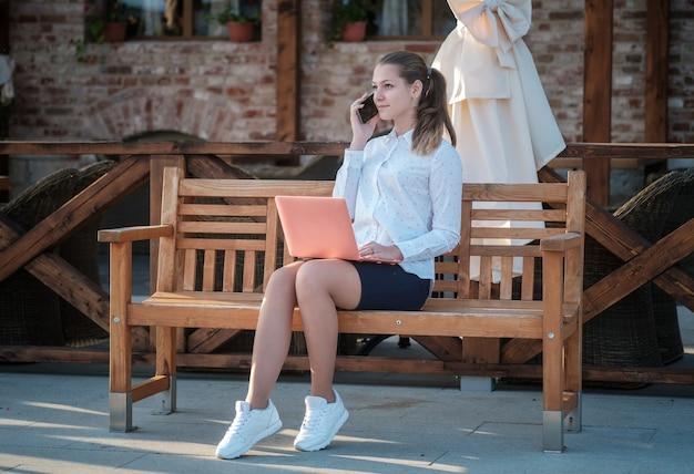 若い美しい女性がベンチに座って、スマートフォンとラップトップを持っています。街の通りでラップトップとスマートフォンを持っている学生