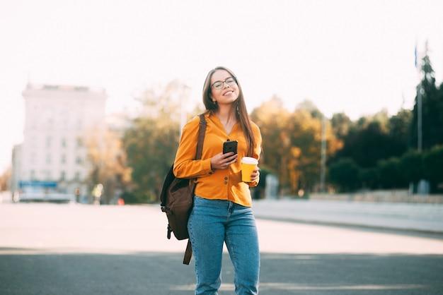 若い美しい女性が街を歩いていて、笑顔が温かい飲み物と彼女の携帯電話を保持しているカメラを見ています