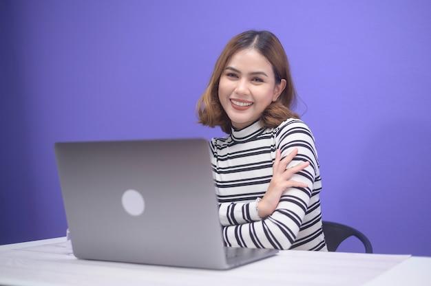 Молодая красивая женщина работает со своим компьютером на синем фоне.