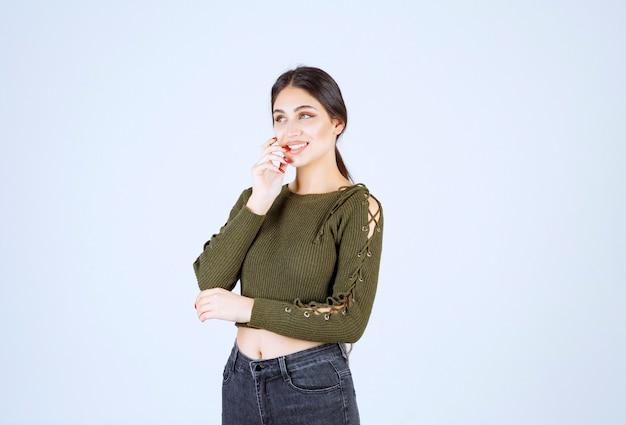 幸せを感じる緑のブラウスの若い美しい女性モデル