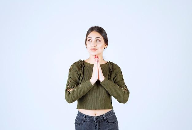 Модель молодой красивой женщины смотрит вверх во время молитвы