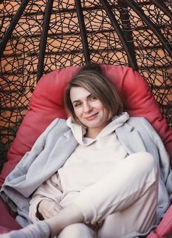 Молодая красивая женщина отдыхает на природе в кресле. прохладная погода