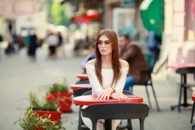夏のカフェのテーブルに座っている若い美しい女性