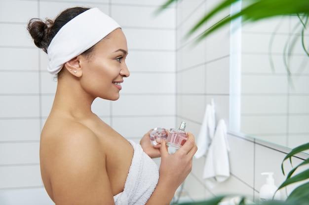 若い美しい女性は、彼女の手にボトルの香水(香水)を持って鏡の前に立っています