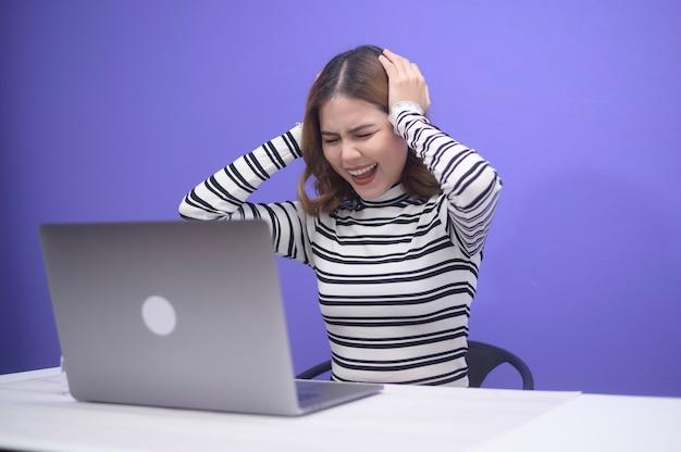 Молодая красивая женщина подчеркнула без работы на синем, концепции психического здоровья