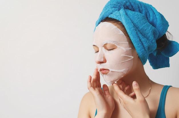 아름 다운 젊은 여자는 그녀의 머리를 감싸 수건으로 보습 화장품 직물 얼굴 마스크를 사용합니다. 흰 벽에.