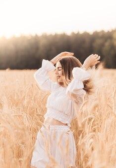 若い美しい女性が白い服を着て麦畑を歩く