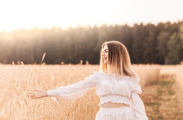 Молодая красивая женщина идет по пшеничному полю в белой одежде