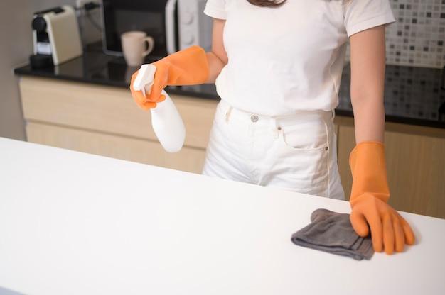 Молодая красивая женщина в защитных резиновых перчатках чистит стол на кухне дома.