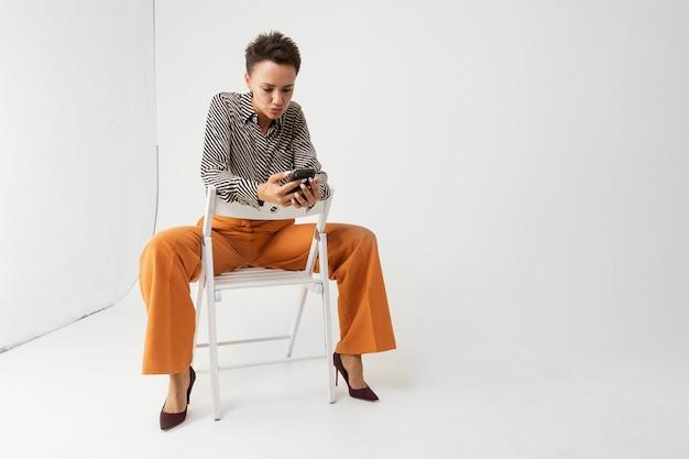 Молодая красивая женщина с короткими темными волосами, макияж в черно-белой полосатой рубашке, коричневые брюки и туфли сидит на стуле с телефоном в руках и думает