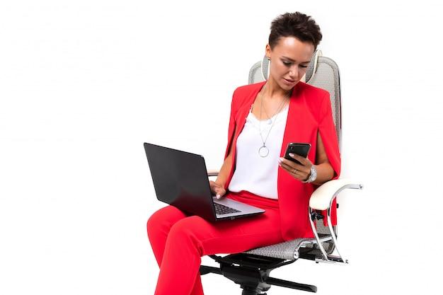 Молодая красивая женщина с короткими темными волосами, макияж в красном офисном костюме, дорогие часы, сидит в компьютерном кресле с ноутбуком и телефоном в руке