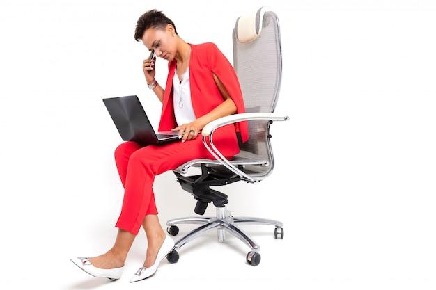 Молодая красивая женщина с короткими темными волосами, макияж в красном офисном костюме с бижутерией, дорогие часы, сидит в компьютерном кресле с ноутбуком и телефоном в руке