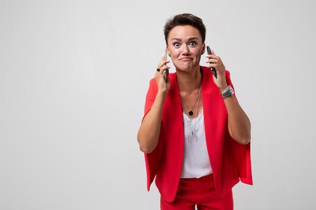 Молодая красивая женщина с короткими темными волосами, макияж в красном офисном костюме с бижутерией, часы и телефон